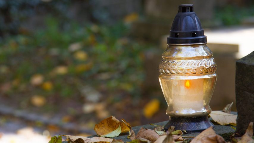 Votive candles at the grave with autumn leaves.